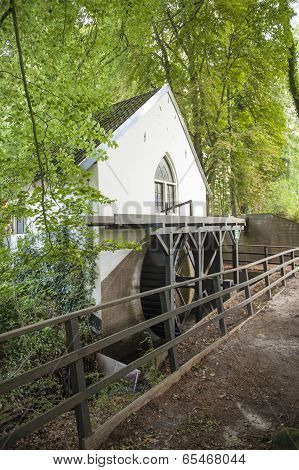 Traditional water mill with waterwheel in forest scenery stock photo
