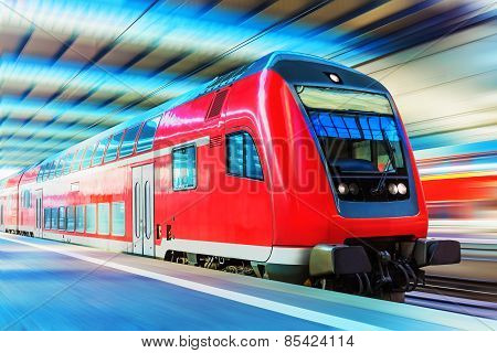 Scenic view of red modern high speed passenger commuter double decker train on tracks at the station platform with motion blur effect stock photo