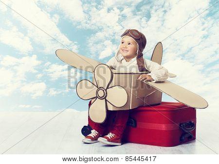 Little Child Playing Airplane Pilot, Kid Traveler Flying In Aviator Helmet On Travel Suitcase