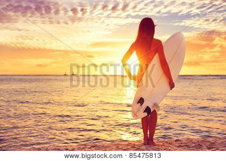 Surfer girl surfing looking at ocean beach sunset. Beautiful sexy female bikini woman looking at wat