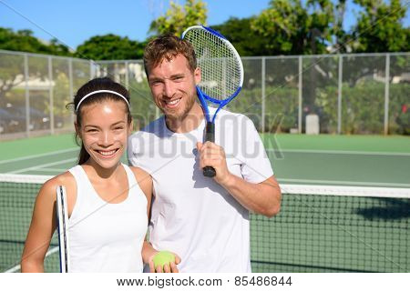 Tennis players portrait on tennis court outdoor. Couple or mixed double tennis partners after playin