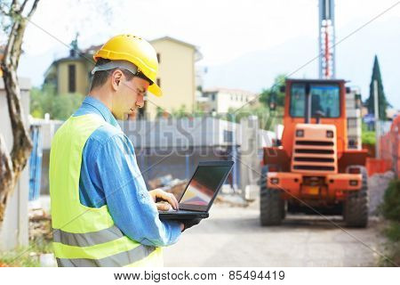 construction worker in safety protective work wear with laptop computer  at construction site in fro