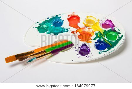 different size paint brushes and color palette. Paints smeared on a palette. Light background with brushes and paint stock photo