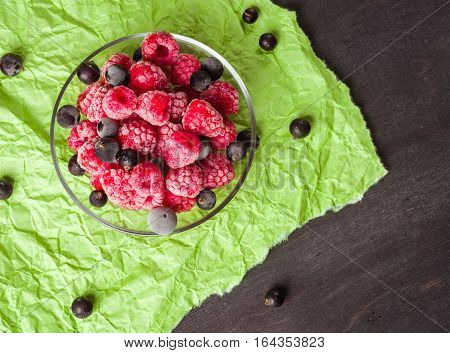 Frozen raspberries in a glass saucer. Frost on the berries. Dark and green background. Green crumpled paper. stock photo