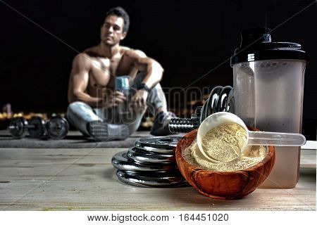 Protein shake Vanilla flavor accompanied by weights and sportsmen in the background stock photo