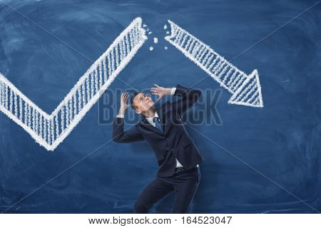 Businessman cowering on blue blackboard background with chalk drawing of white statistic arrow broken in half. Business management. Profit and loss. Business and success. stock photo