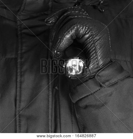 Gloved Hand Holding Tactical Flashlight, Bright Light Emitting Brightly Lit Serrated Strike Bezel, Black Grain Leather Glove And Cop Jacket, Large Detailed Vertical Closeup, Patrolling Police Security Guard Staff Policeman, Covert Operations stock photo
