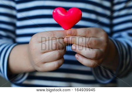 child holding a small pink heart. symbol of love family hope. Backgrounds for cards on Valentine's Day. Backgrounds for social posters about the preservation of the family and children.
