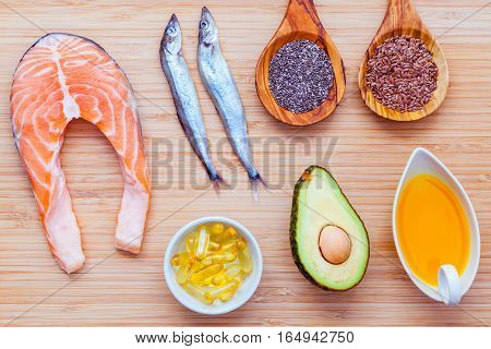 Selection food sources of omega 3 and unsaturated fats. Super food high vitamin e and dietary fiber for healthy food. Olive oil flax seed chia fish oil avocado shishamo fish and salmon on bamboo cutting board. stock photo