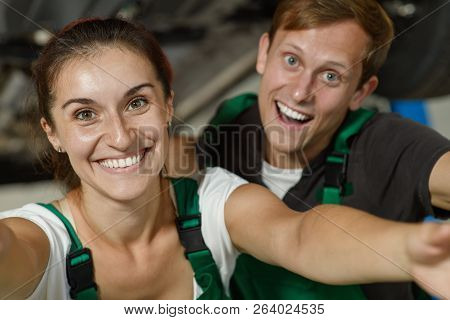 A beautiful and young girl locksmith doing selfie with her colleague from the car service stock photo