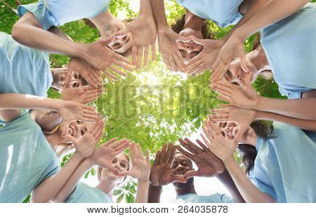 Happy team of volunteers putting hands in circle, copy space stock photo