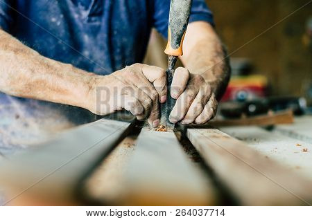 Professional carpenter at work, he is carving wood using a woodworking tool, hands close up, carpentry and craftsmanship concept stock photo