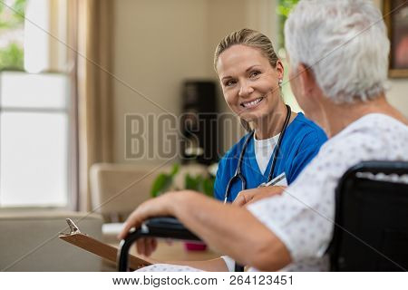 Friendly doctor examining health of patient sitting in wheelchair. Happy smiling nurse consulting di
