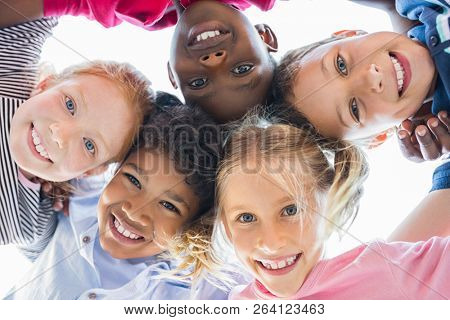 Closeup face of happy multiethnic children embracing each other and smiling at camera. Team of smili