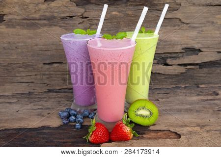 Strawberry kiwi and blueberry smoothies smoothies juice beverage healthy the taste yummy In glass drink episode morning on wooden background. stock photo