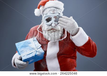Frozen Santa Claus with christmas present removing snow from goggles stock photo