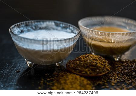 Home remedy for seborrhea dermatitis hair loss on wooden surface i.e. Curd with water and flax seed powder in a glass container with raw flax seed,Close up view. stock photo