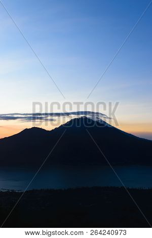 Sunrise view from Gunung Batur volcano in Bali, Indonesia with visible silhouette of Mount Agung volcano peak covered with clouds stock photo