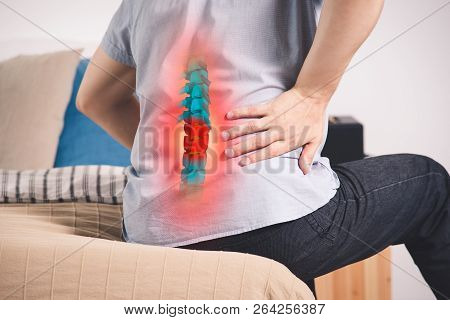 Pain In The Spine, A Man With Backache At Home, Injury In The Lower Back, Photo With Highlighted Ske