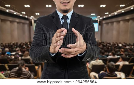 Closeup Businessman clapping and smiling on Abstract blurred photo of conference hall or seminar room with speakers on the stage and attendee background, business learning success concept stock photo