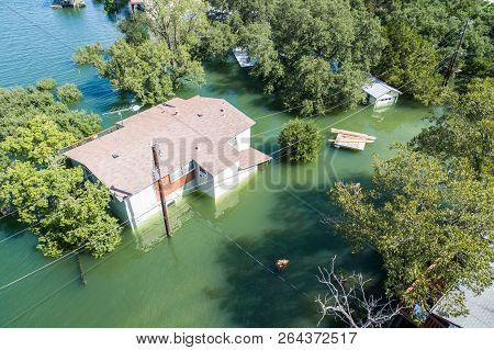 aerial drone view of Historic flooding home under water or house under flood water , Lake Travis , outside of Austin ,TX , reflection off the side of the home half way under water stock photo