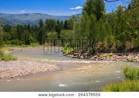 Blue Sky, White Clouds, River Splashing, Flowing Over Rocks. Sunny Summer Day. Ivanovskiy Khrebet Ridge, Altai Mountains, Kazakhstan.  Tilt-Shift Artistic Effect stock photo