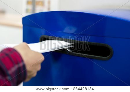 close up hand drop letter and documents in the blue postbox in post office mail stock photo