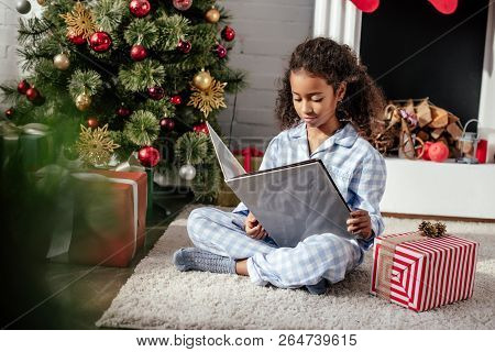 adorable african american child in pajamas reading book near christmas tree at home stock photo