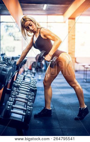 Sexy tanned athletic fitness woman doing exercises for back and posing in the gym stock photo