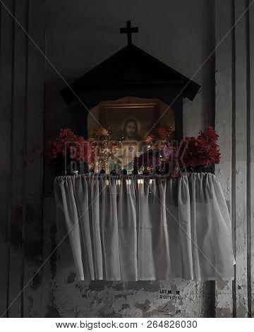Wayside shrine in Praga, Warsaw, Poland, dark moody stock photo