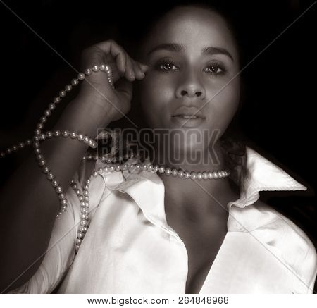 A beautiful Glamour Girl on Black with pearls stock photo