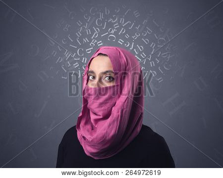 Young muslim woman wearing niqab with white alphabet letters above her head stock photo