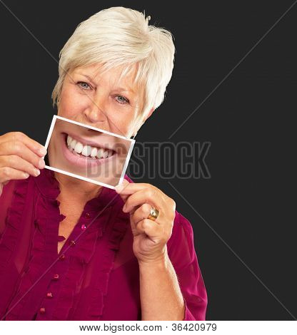 Senior Woman With Magnifying Glass Showing Teeth On Black Background stock photo
