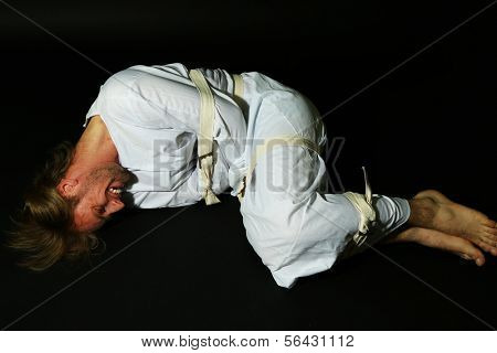 Mentally ill man in strait-jacket on black background stock photo