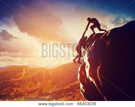 Hikers climbing on rock, mountain at sunset, one of them giving hand and helping to climb. Help, sup
