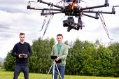 Professional group of a picture taker and pilot working a UAV Photography Drone