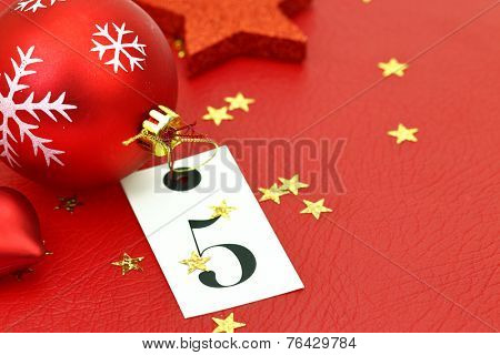 Number five on tag and Christmas ornamets on red background stock photo