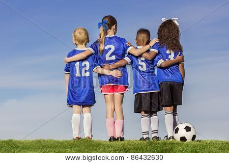 Diverse group of boys and girls soccer players standing together with a ball against a simple blue s