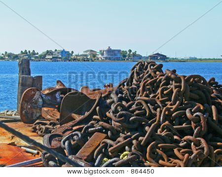 anchor and chain on the edge of the water stock photo