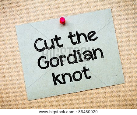 Cut the Gordian Knot Message. Recycled paper note pinned on cork board. Concept Image stock photo