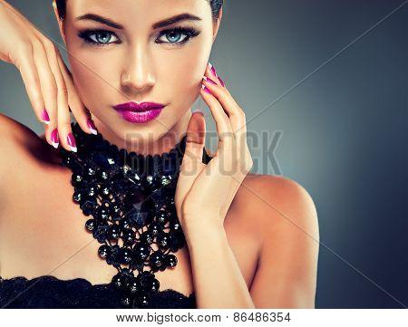 Model with fashionable nail Polish fuchsia and black necklace