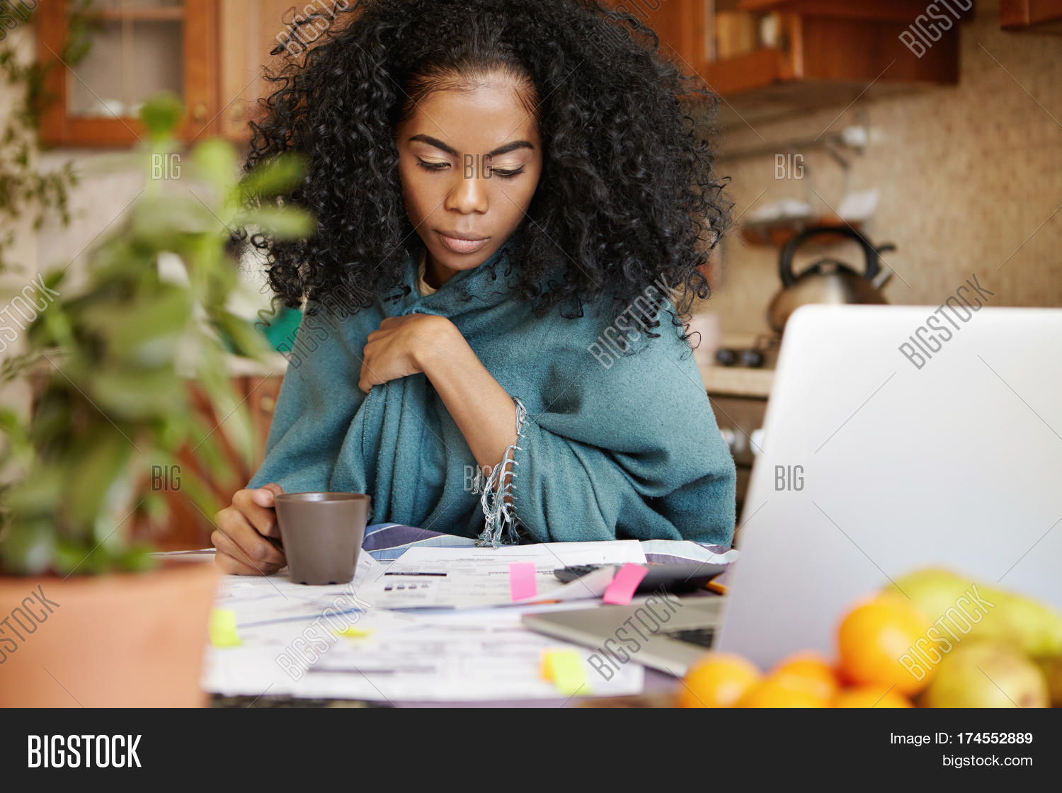 Upset dark-skinned housewife with Afro hairstyle having coffee while managing domestic budget late at night calculating family expenses paying bills online having tired and concentrated look