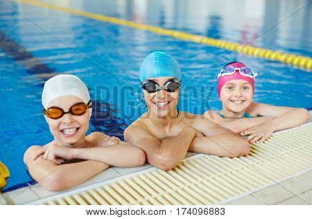 Three healthy smiling children looking to camera wearing swimming goggles and caps in water at tiled border of blue clearwater swimming pool stock photo