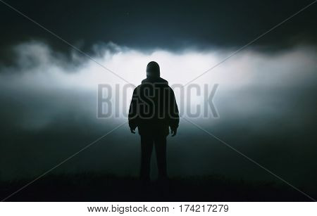 Silhouette of a man in the darkness. Night Photography. Dense fog over the river with man silhouette. Silhouette in dark night background
