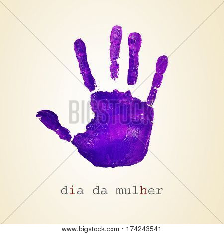 a violet handprint and the text dia da mulher, womens day in portuguese, on a beige background stock photo