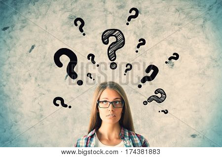 Pretty caucasian girl with question marks on concrete wall background. Questions concept