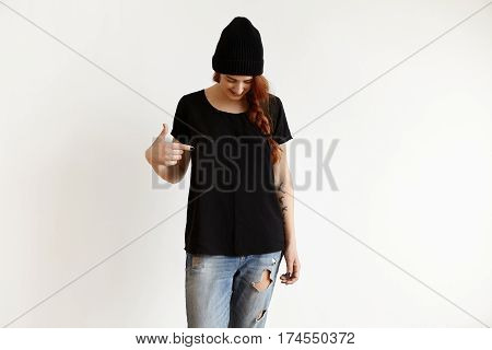 Fashion clothing and design concept. Studio shot of fashionable Caucasian girl in stylish hat and ragged blue jeans looking down and pointing index finger at copy space on her black loose t-shirt stock photo