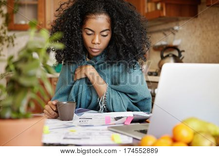 Upset dark-skinned housewife with Afro hairstyle having coffee while managing domestic budget late at night calculating family expenses paying bills online having tired and concentrated look stock photo