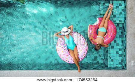 Two people (mom and child) relaxing on donut lilo in the pool at private villa. Summer holiday idyll