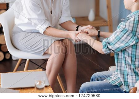 Lend credence. Two persons sitting on the chairs having bracelets on wrist while holding tight stock photo